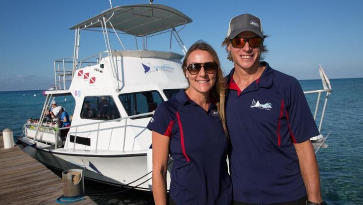 picture of the two owners of Living the dream divers standing together with boat in background