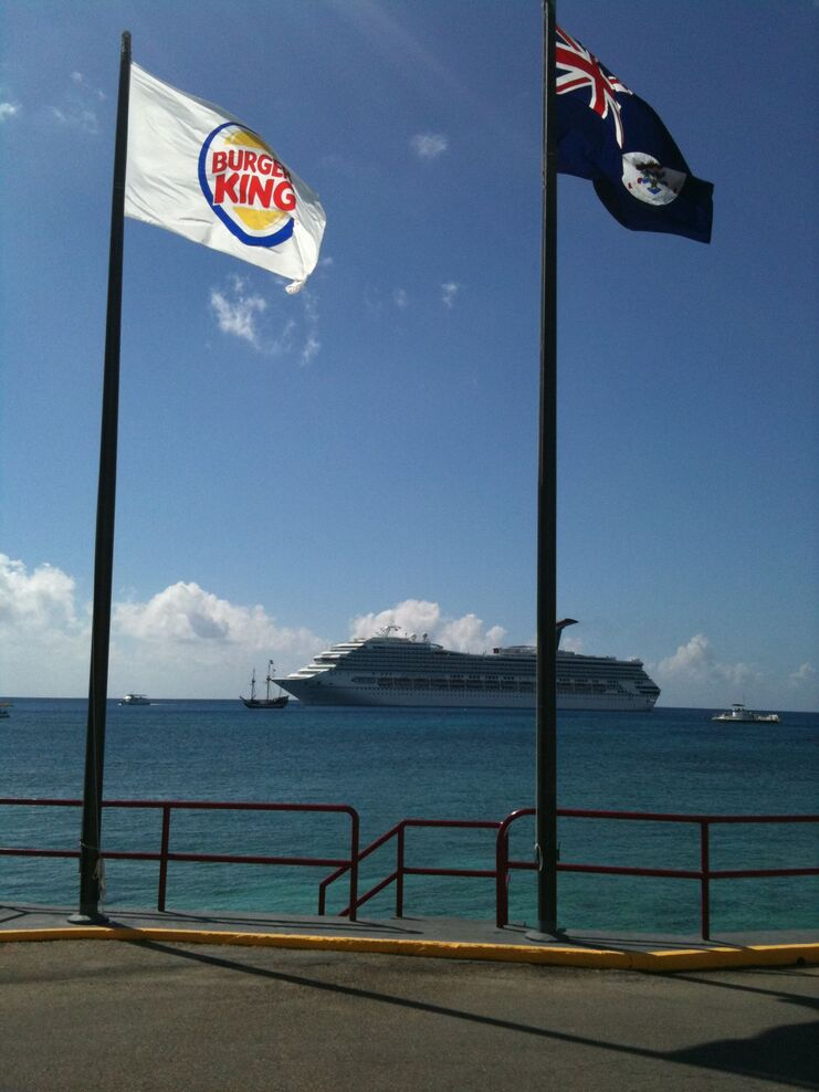 picture of the burger king flag an cayman islands flag with cruise ship in the background
