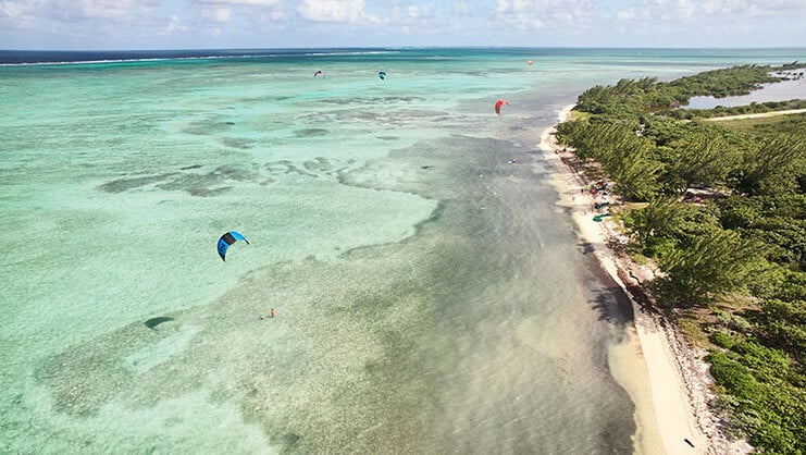 picture of barkers beach from air with people kitesurfing in the distance