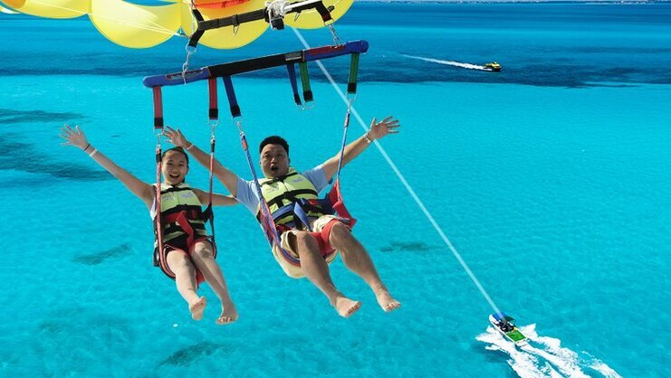picture of two people parasailing high in the sky