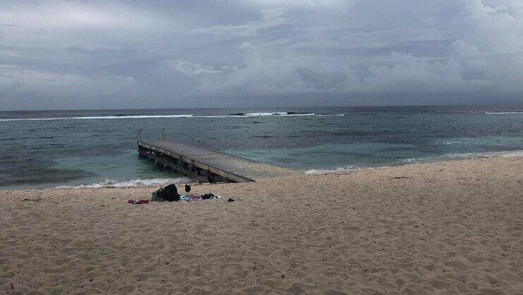 picture of spotts beach with dock in middle and barrier reef in background