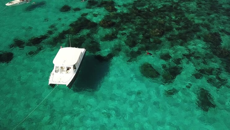 picture of boat with coral in background