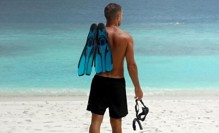 person standing on beach holding snorkel, mask and fins
