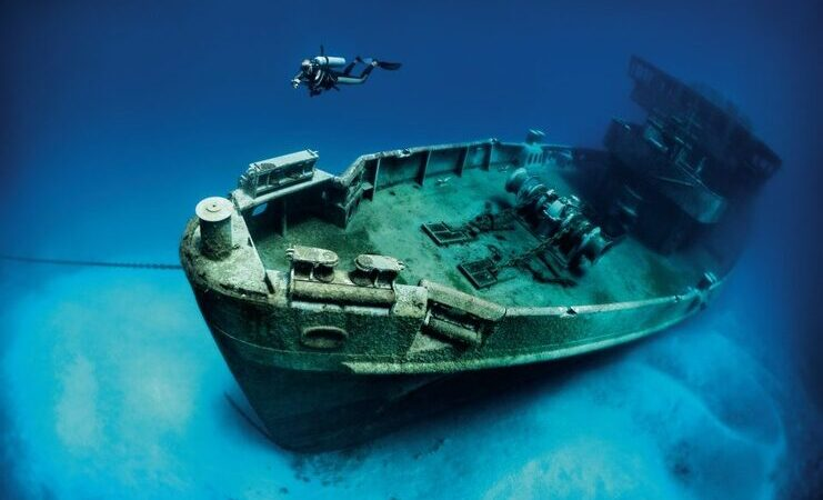 picture of person scuba diving with kittiwake shipwreck in the background