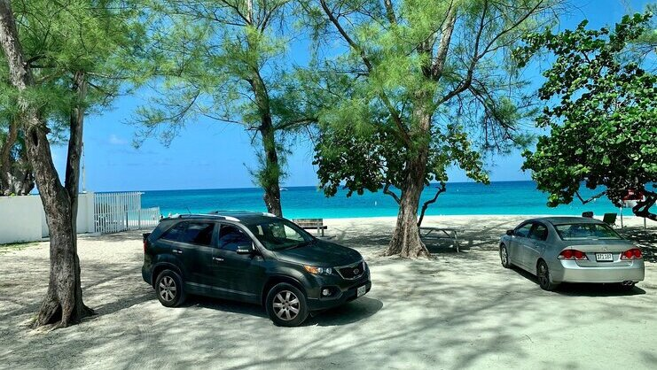 picture of two cars with beach in background