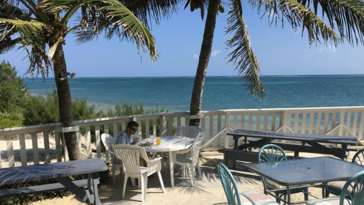 picture of man eating by himself at a table with sea in background
