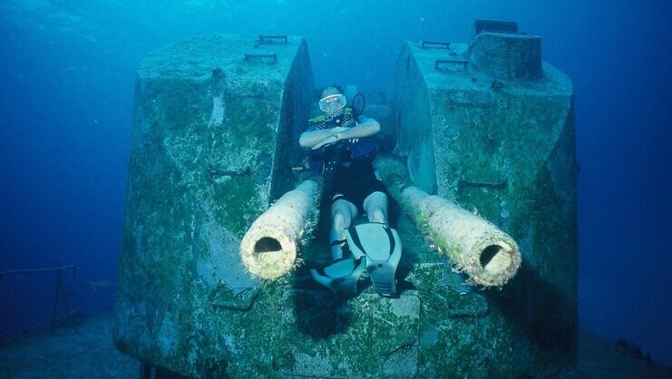 picture of diver underwater sitting on top of large gun from sunken ship