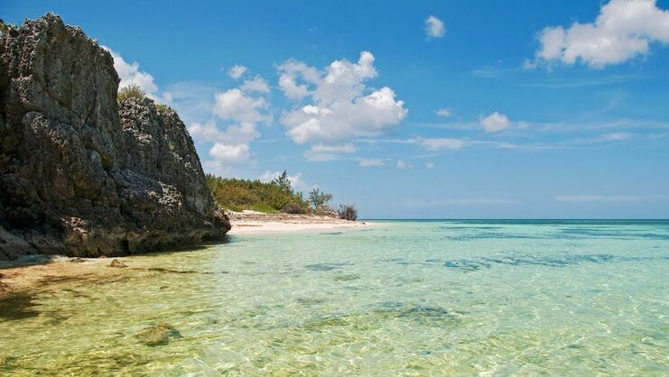 picture of 20 foot tall cliff at barefoot beach with shallow water