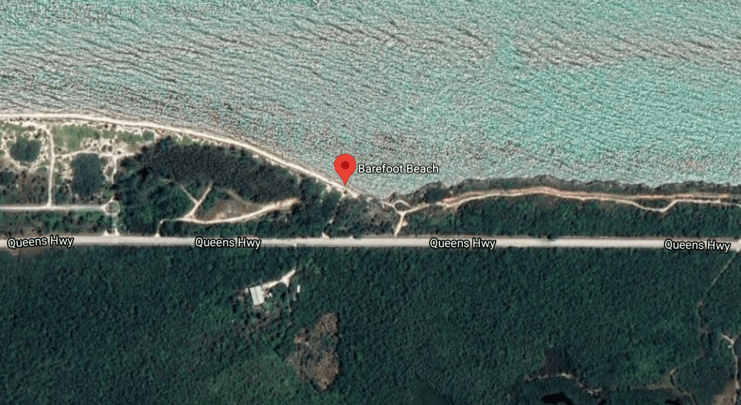 aerial image showing road next to barefoot beach